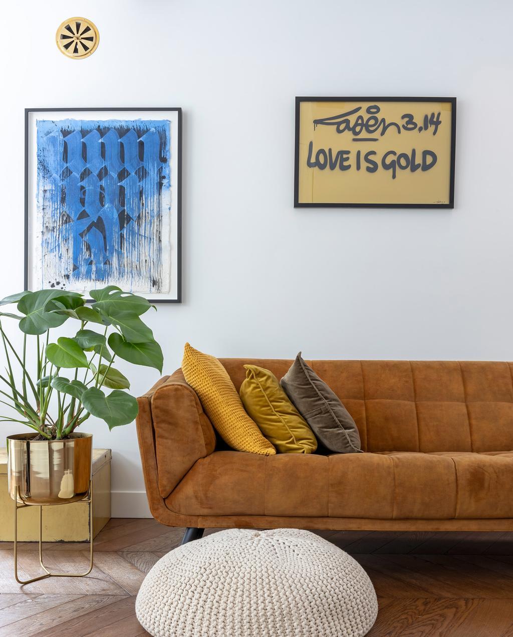 vtwonen special tiny houses | bank in de woonkamer met kunstwerk met love is gold