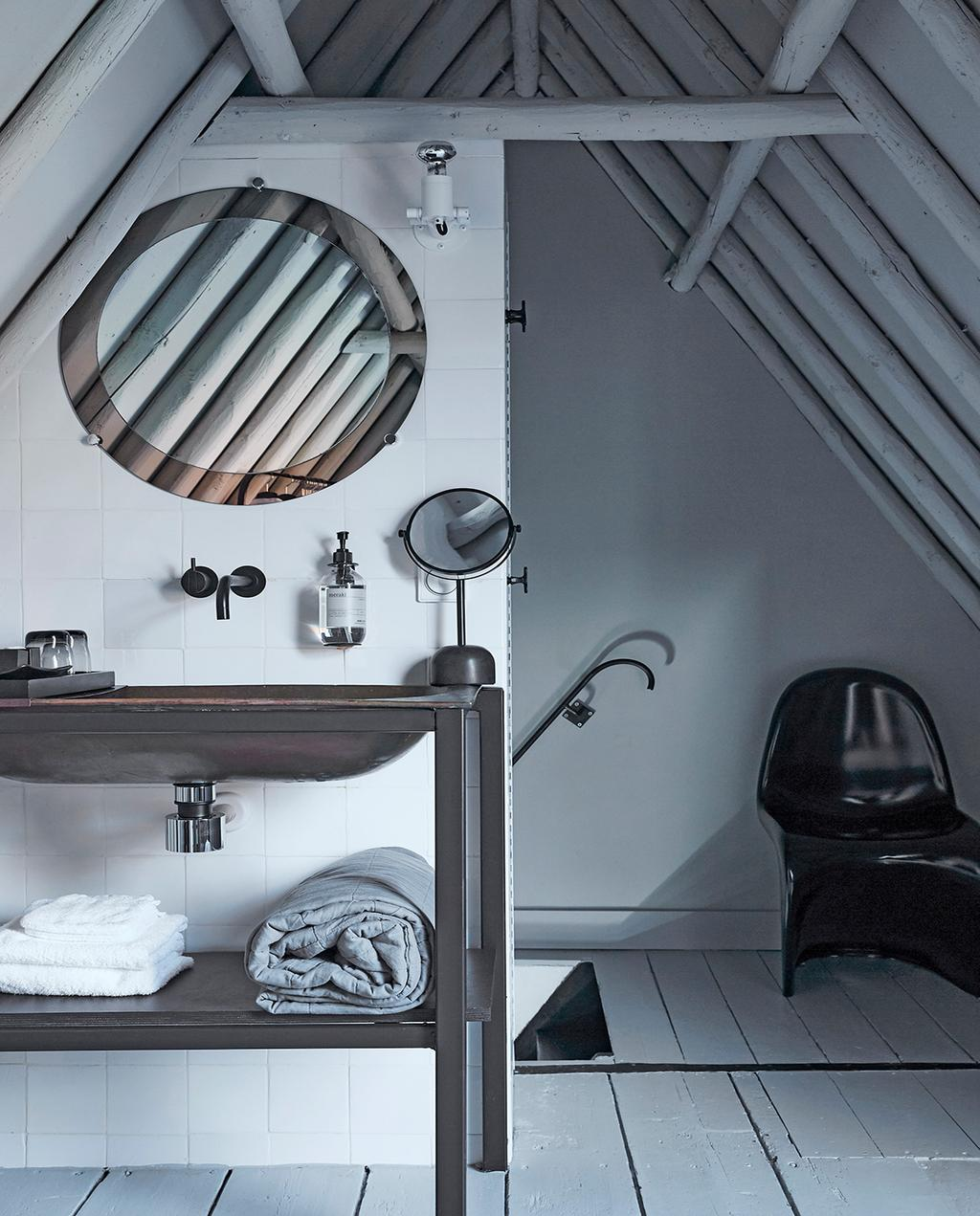 vtwonen 02-2021 | binnenkijken Harlingen badkamer met wit schuin dak, zwarte stoel