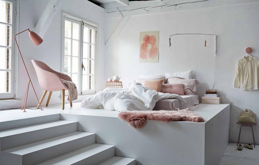 Wit bed met roze accessoires in slaapkamer