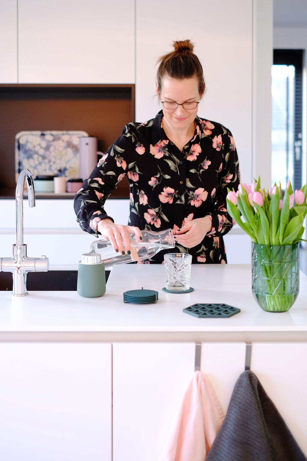 Onderzetters en zeeppomp in de witte keuken van het voorjaarshuis van PRCHTG