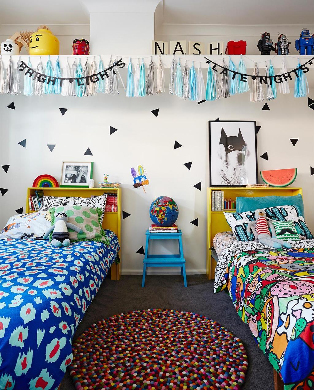 vtwonen binnenkijken special 07-2021 | twee bedden in de kleurrijke kinderkamer met een nachtkastje en een wereldbol, boven het bed hangen blauwe slingers