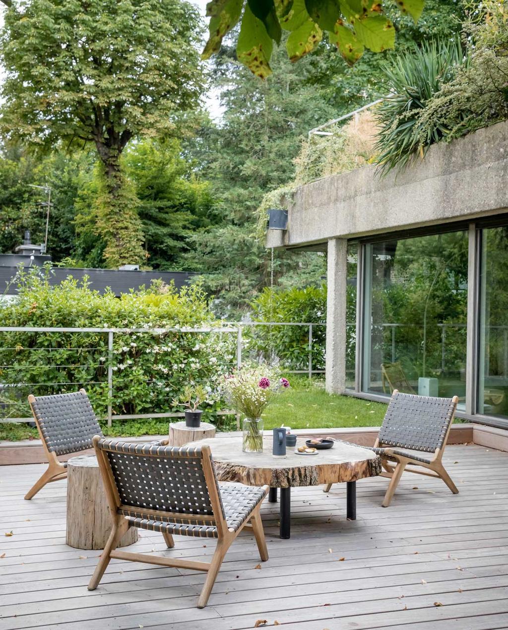 vtwonen 09-2020 | Binnenkijken Frankrijk | tuin | veel groen en een zithoek met lage stoelen en tafel