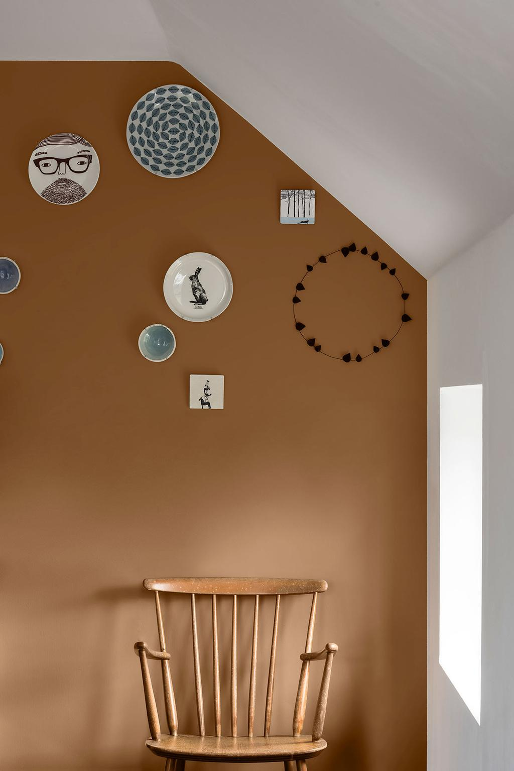 Een muur is geschilderd in de Kleur van het Jaar en gedecoreerd met verschillende borden.