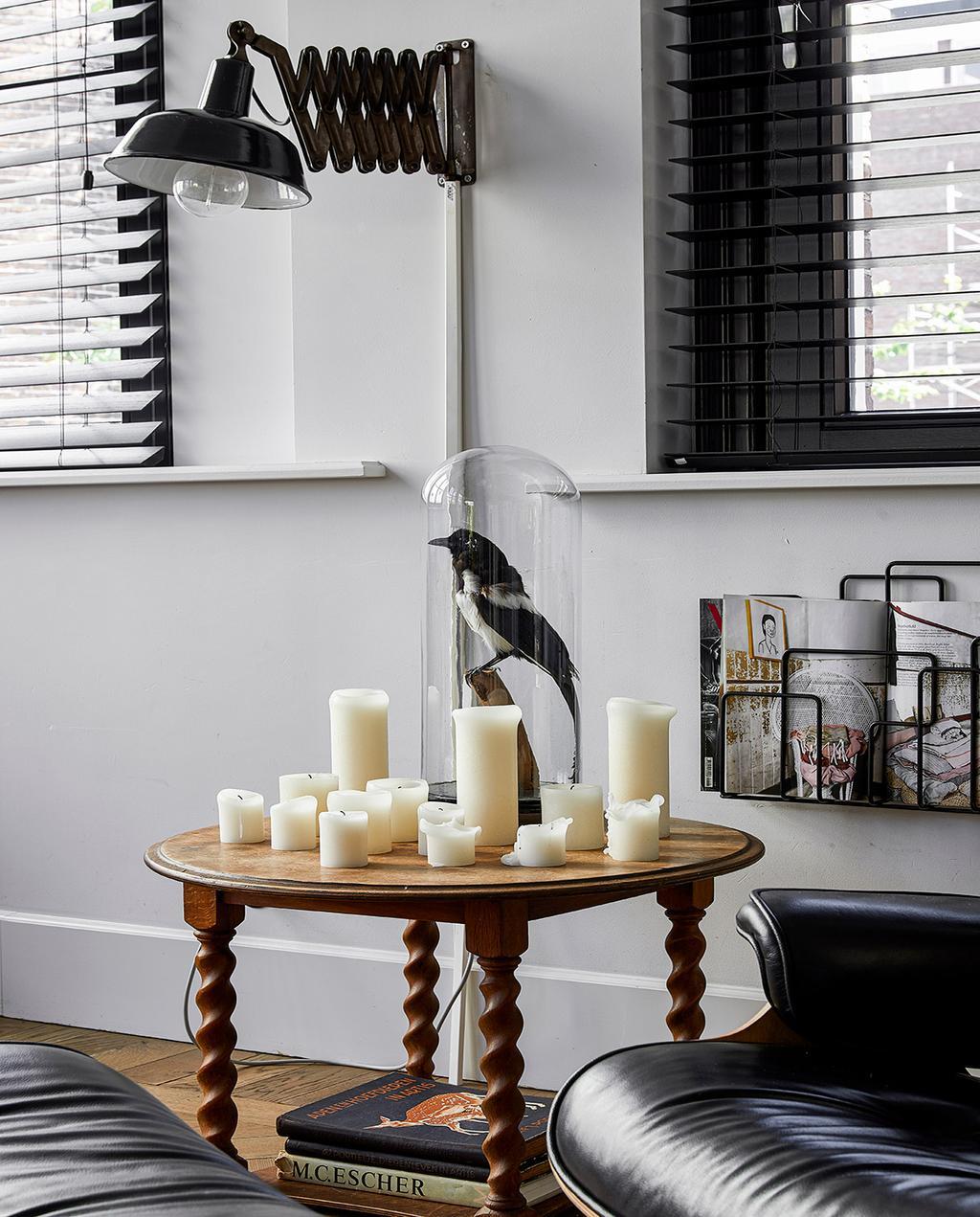 vtwonen 02-2021 | binnenkijken bij Martine kaarsen op een houten tafel, met een opgezette vogel in stolp