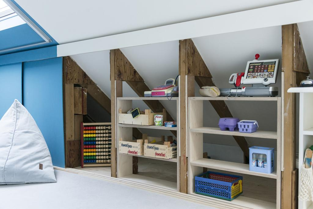 Zolder voor kinderen met schuine wanden en opbergkasten, speelgoed achter schuifdeuren