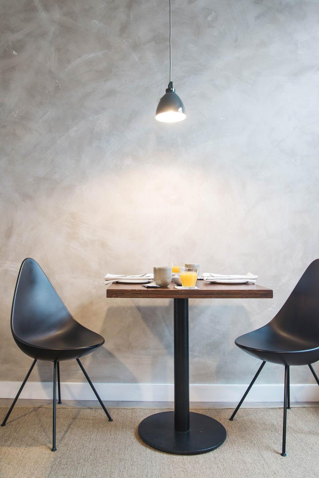 Ontbijten aan de eettafel met zwarte stoelen en betonlook muur in B&B The Doghouse in Brugge