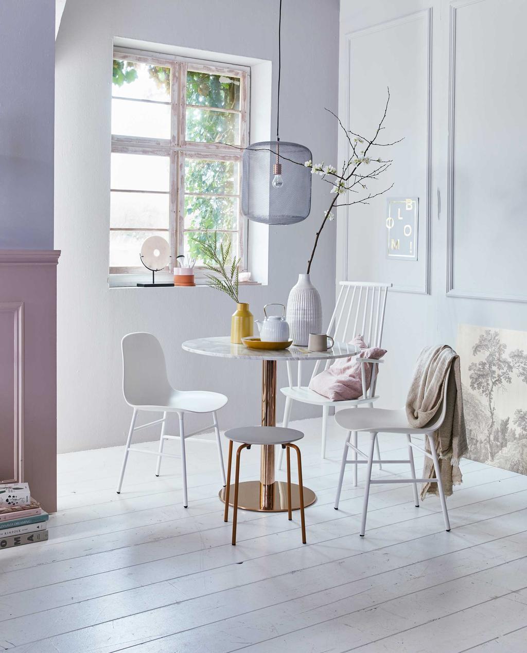Een eetkamer met witte ronde tafel en witte stoelen