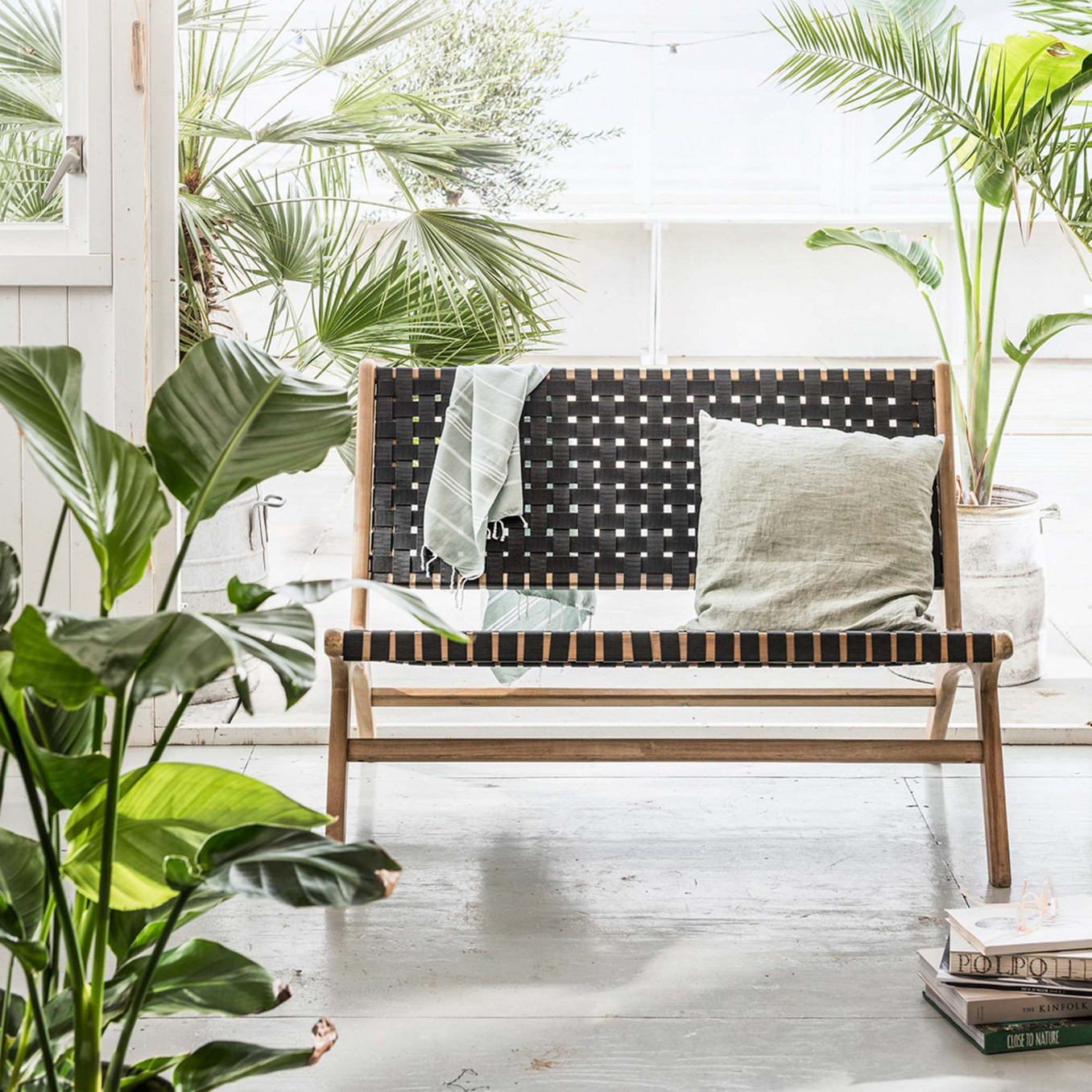 Geweven tuinmeubel met groene planten en witte decoratie-elementen zoals kussens