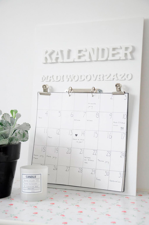 Witte muur en kalender met houten letters.