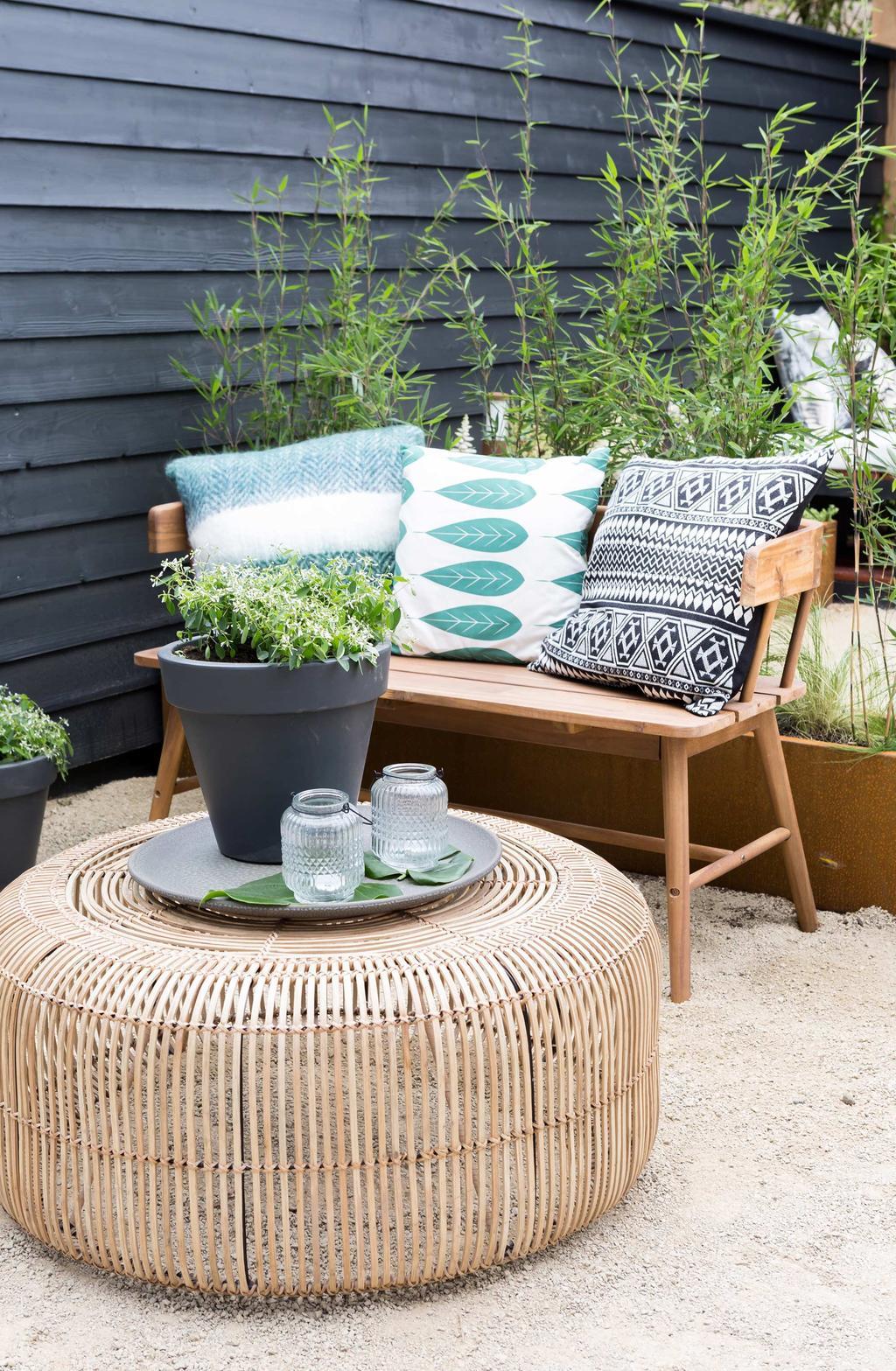 Zithoek in de tuin met houten bank en rotan bijzettafeltje