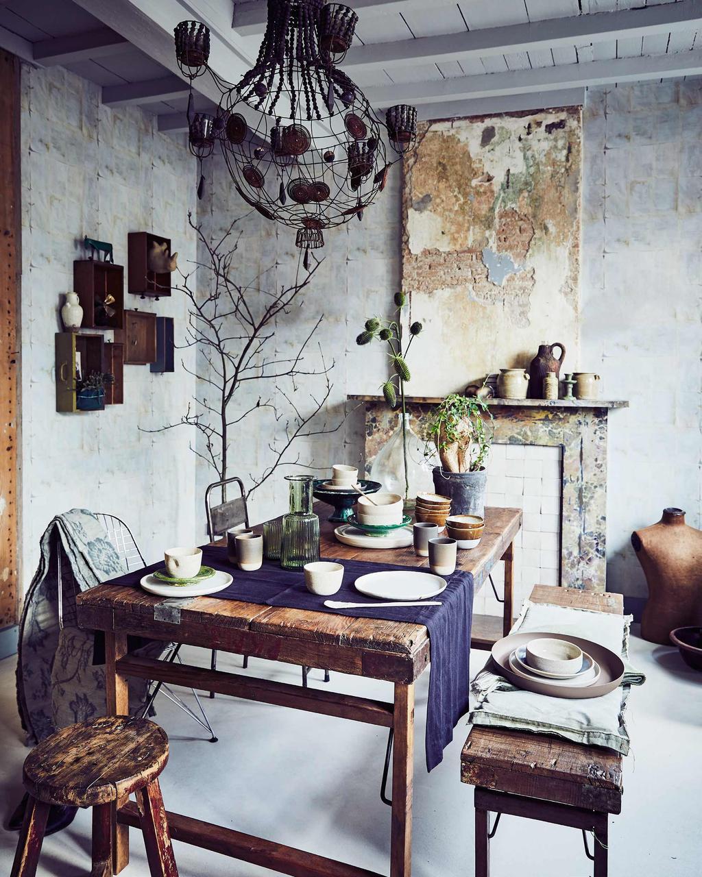 Warm interieur met vintage eethoek met warme materialen en een betonnen muur