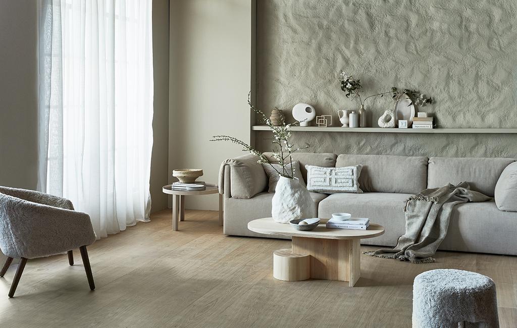 vtwonen 07-2021 | licht huis met half transparante witte gordijnen met een grijze bank een een muur met textuur