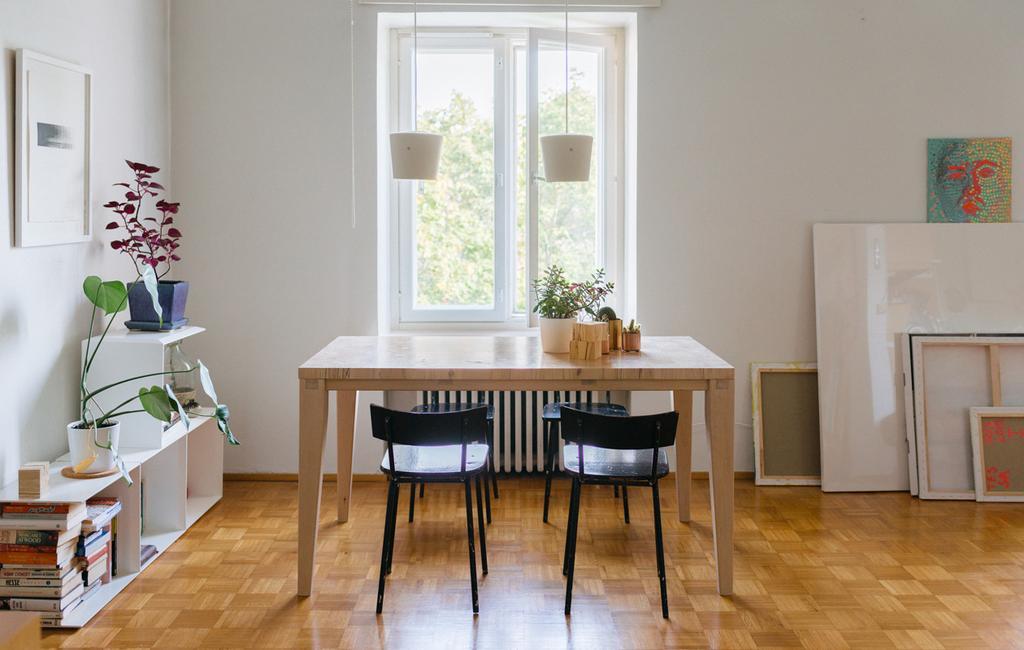studentdesign woonkamer met houten tafel en zwarte stoelen