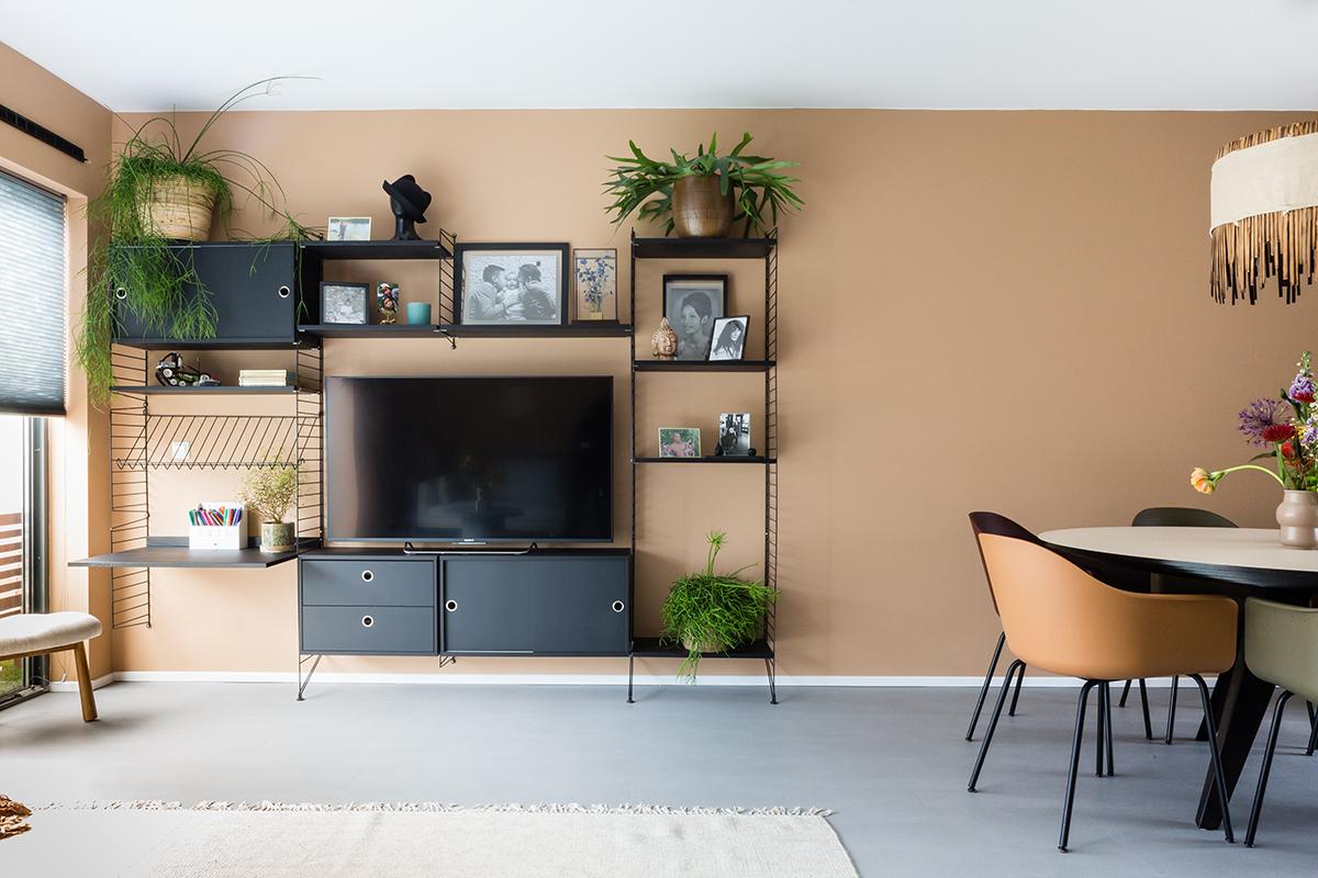 Woonkamer met een zwart wandrek met kastjes een tv fotolijsten en planten