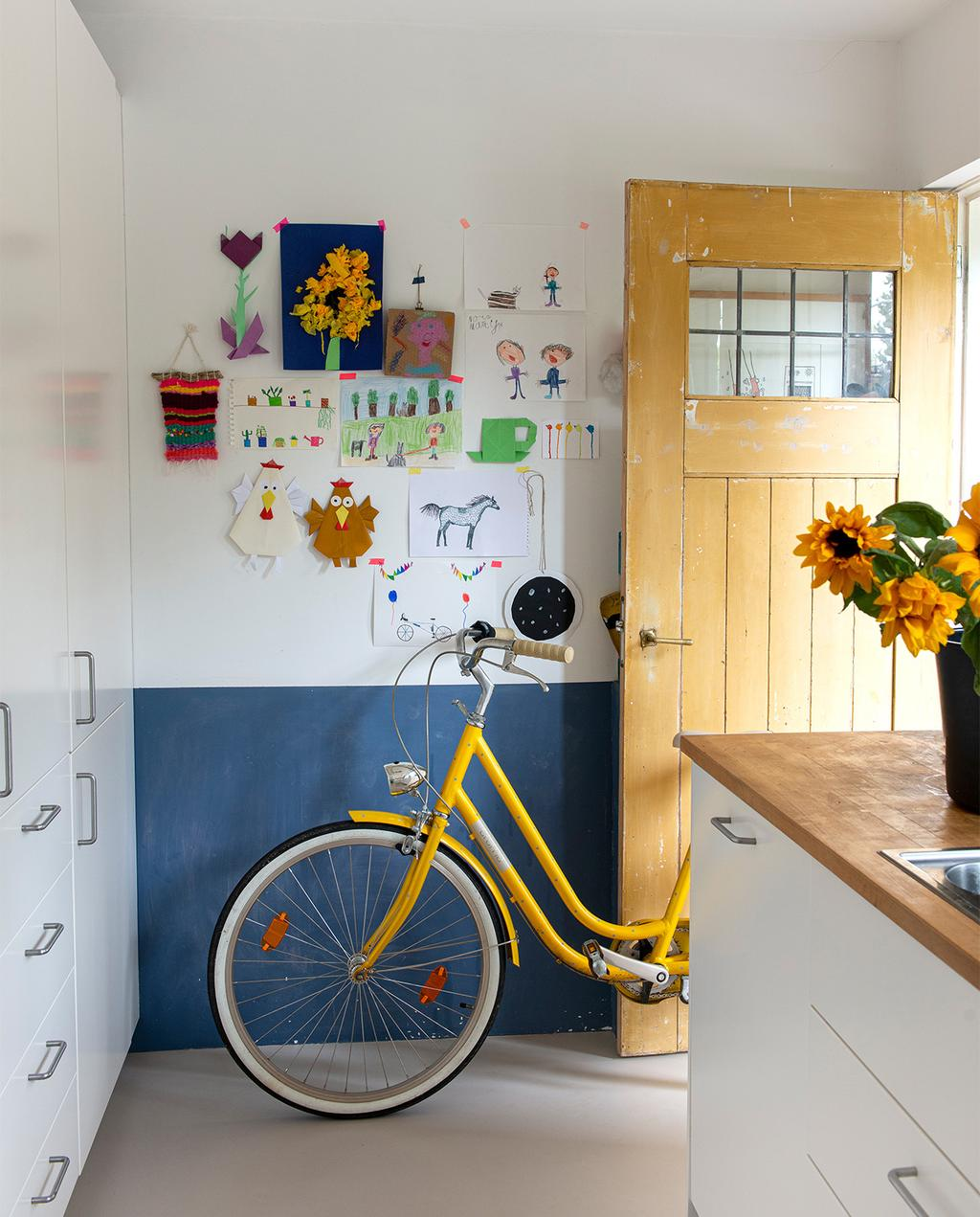 vtwonen 07-2021   blauwe wand met gele fiets en gele deur.