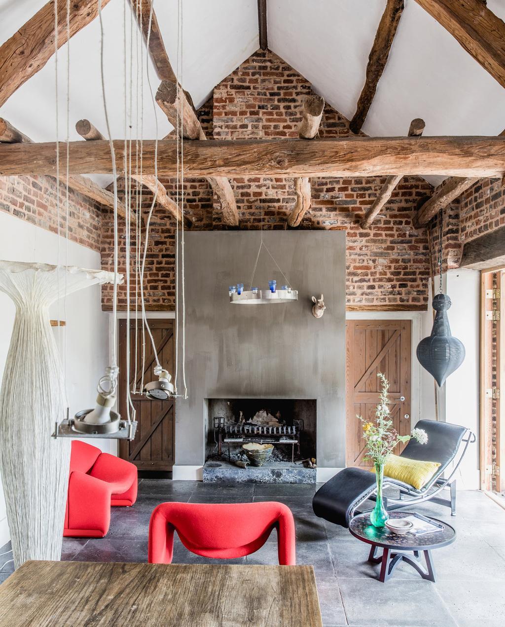 vtwonen 05-2021 | woonkamer met schuin dak en plafond met houten balken en rode fauteuils