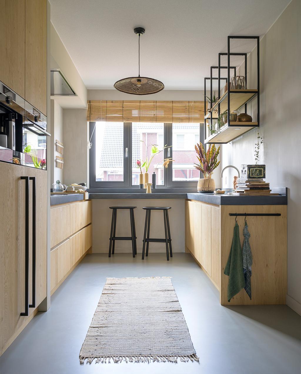 vtwonen 08-2021   houten keuken met zwarte elementen, zoals twee zwarte barkrukken met uitzicht uit het raam, een licht vloerkleed en een houten wandrek