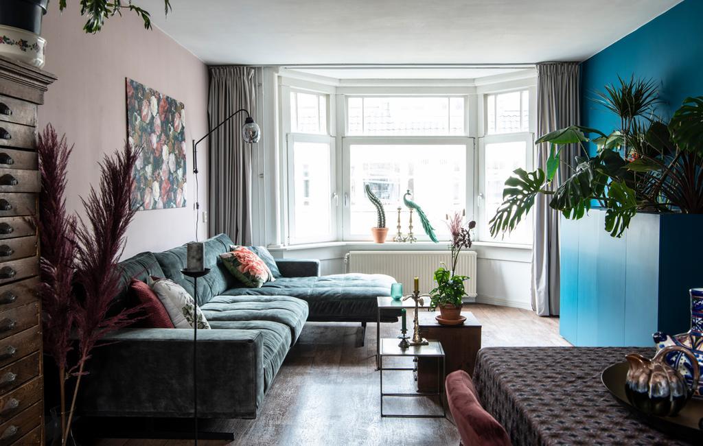Fleurig appartement | woonkamer met groene bank