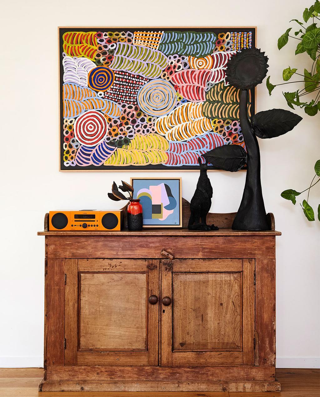 vtwonen binnenkijk special zomerhuizen 07-2021 | houten kast met een kleurrijk kunstwerk, en zwarte ornamenten op de kast