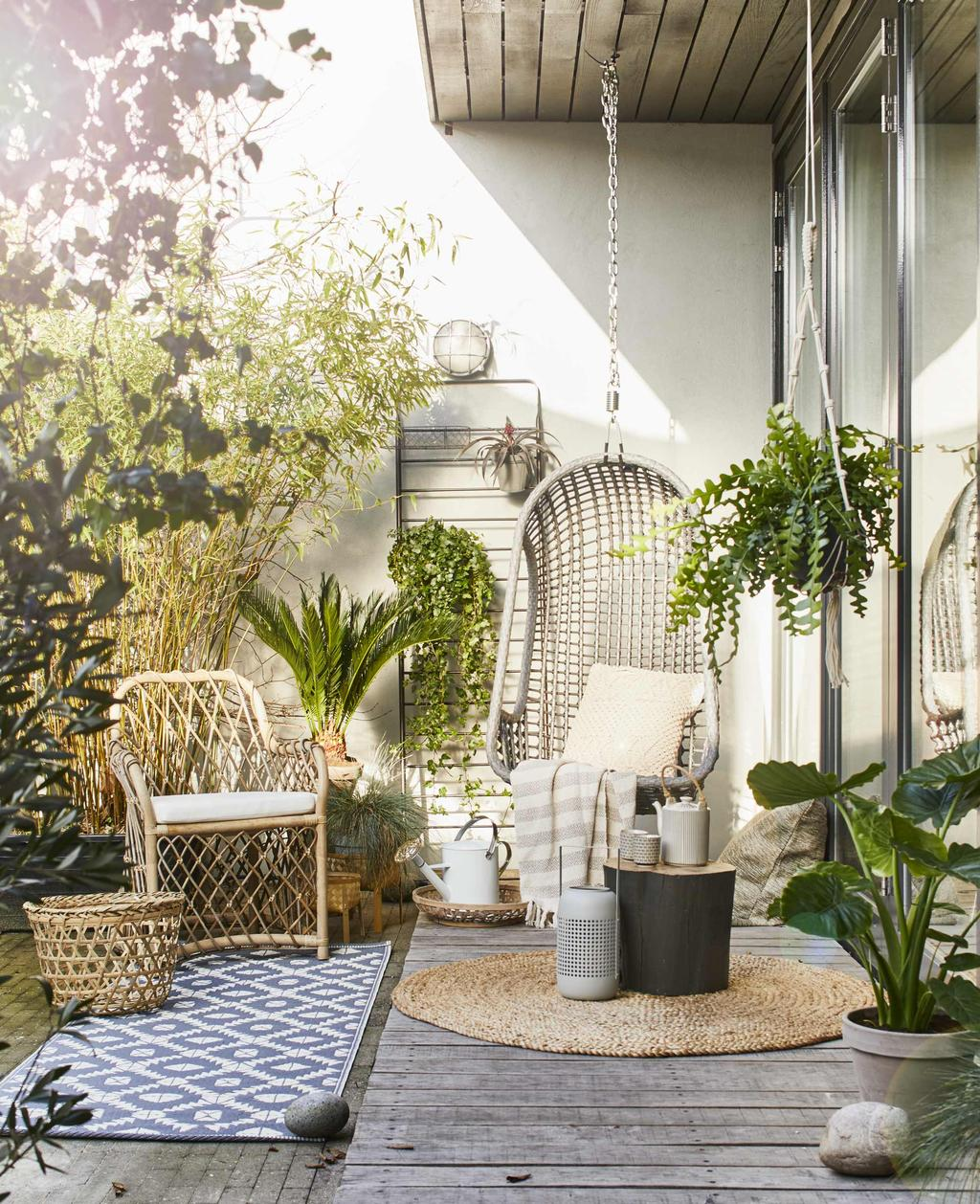 Rotan hangstoel op een terras vol groene planten