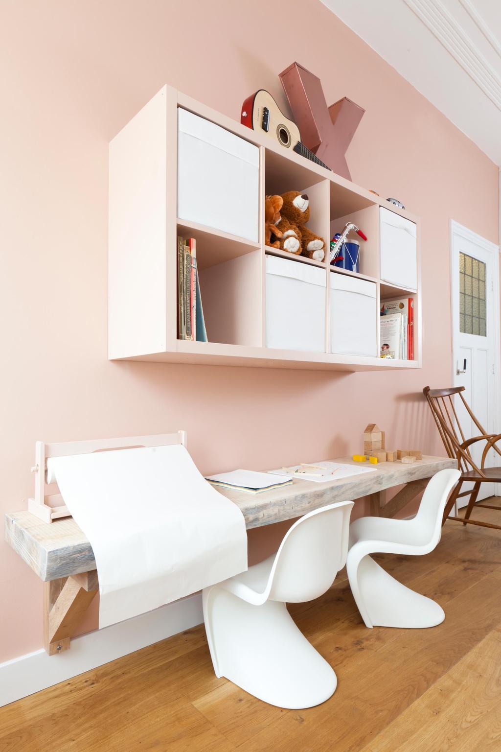 Een licht roze muur met licht roze hoge kast met betonnen bureau
