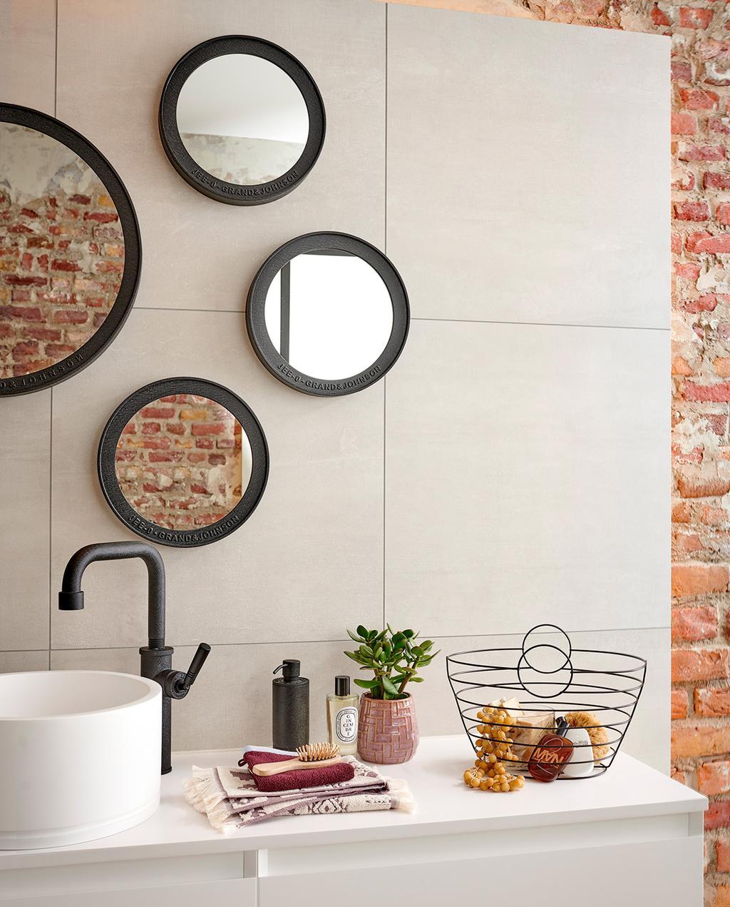 vtwonen special tiny houses | zwarte ronde spiegels in de badkamer op een grijze muur met een bakstenen muur ernaast