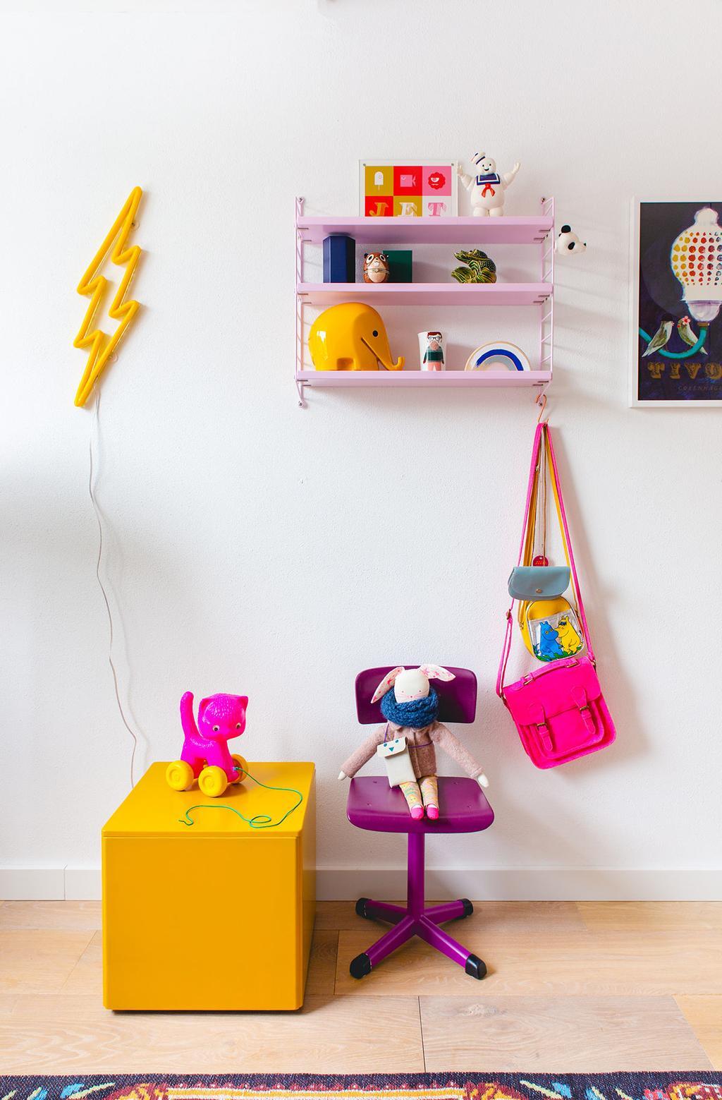 Kleurrijke kinderkamer met paarse kinderstoel, gele bak en roze wandrek
