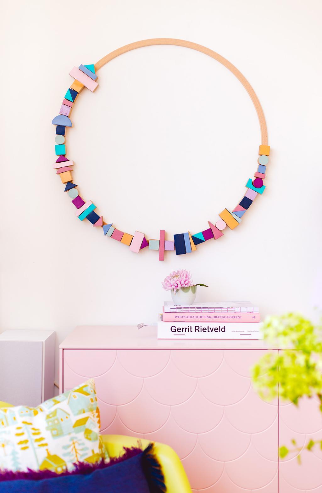 Blokjeskrans op de muur met roze dressoir