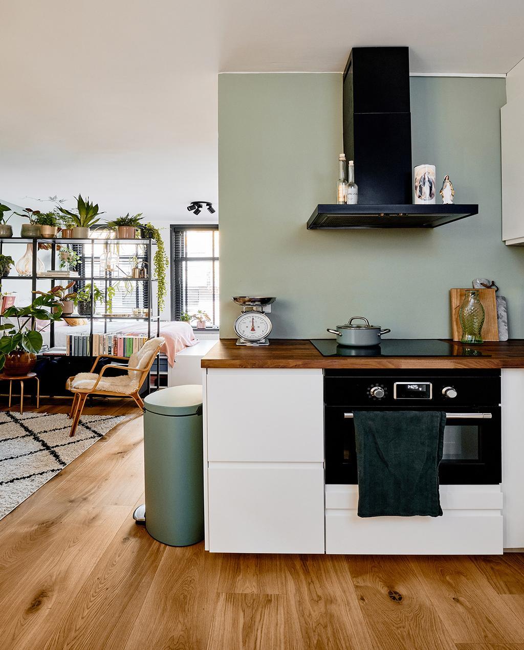 vtwonen 02-2021 | witte keuken overlopend in de woonkamer groene prullenbak