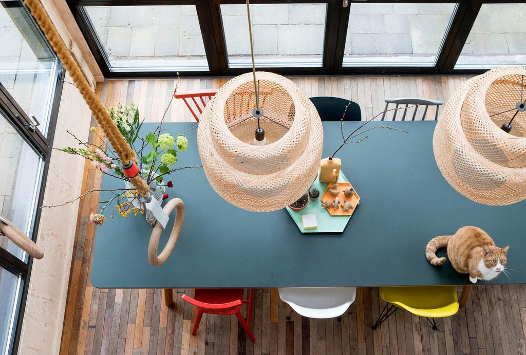 Turqoise eettafel met rotan hanglampen en gym ringen in de keuken
