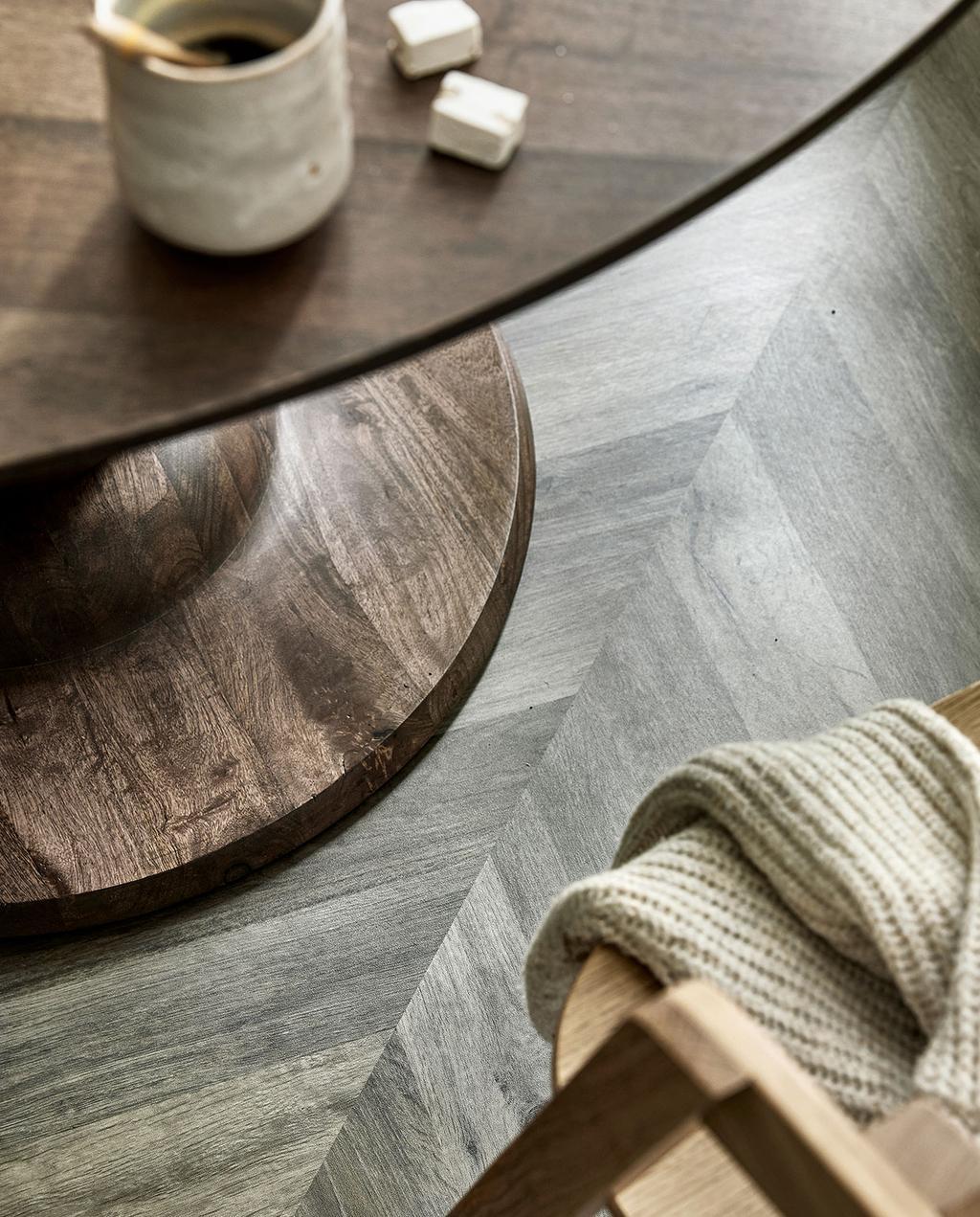 vtwonen 07-2021 | Hongaarse punt patroon vloer met ronde houten tafel, de vloer is de zoethout versie van de Novilon vloeren