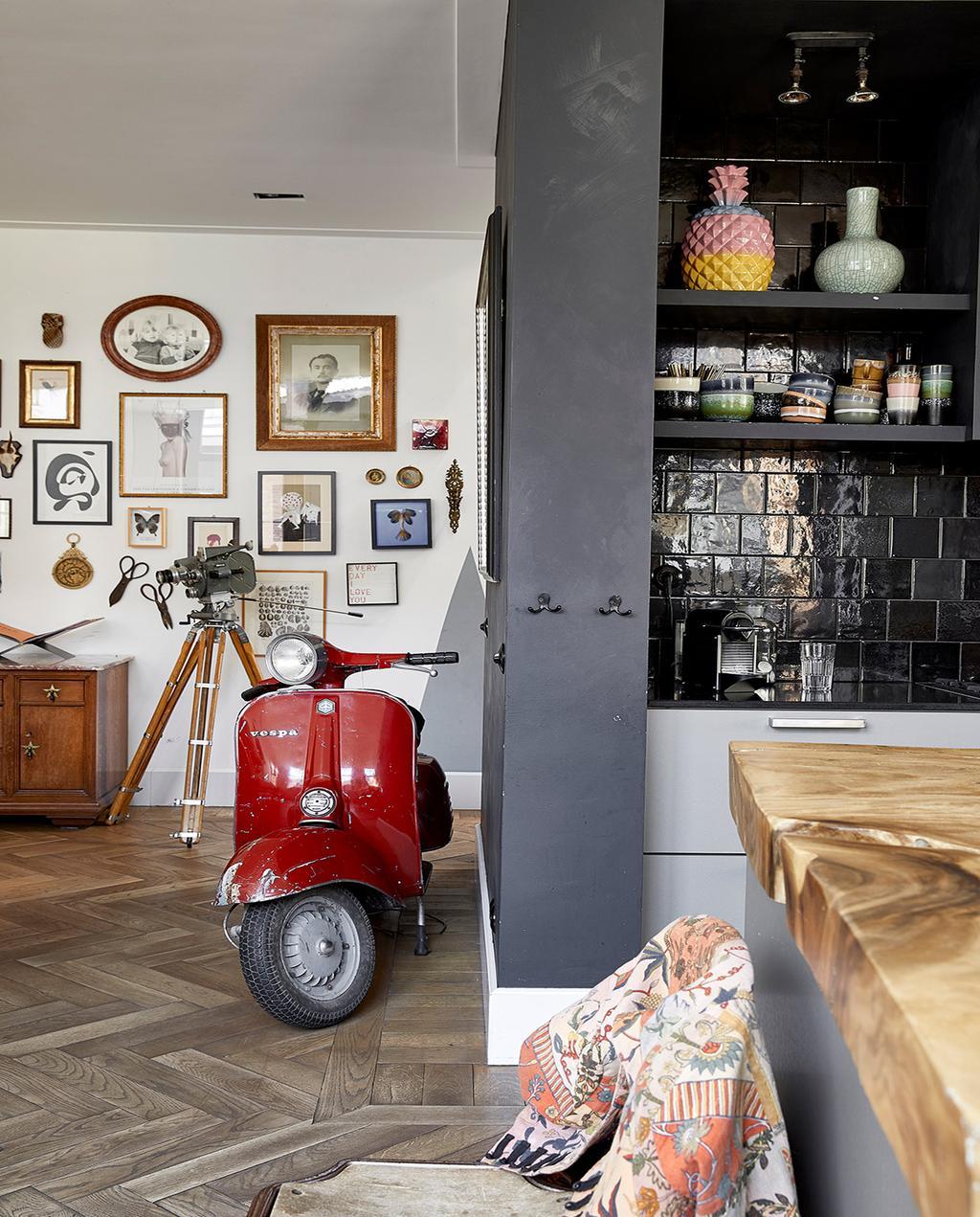 vtwonen 02-2021 | binnenkijken bij Martine, een rode vespa in de woonkamer met fotolijsten op de achtergrond