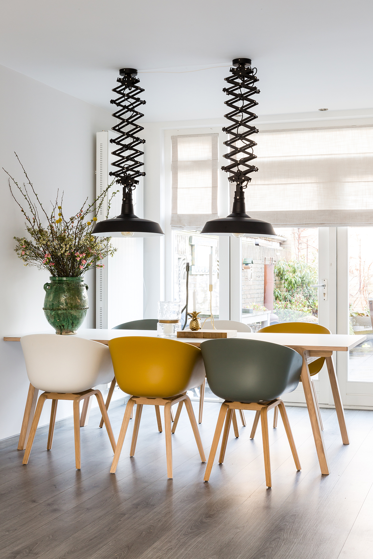 Dezelfde eettafelstoelen in verschillende kleuren aan een tafel met zwarte hanglampen erboven