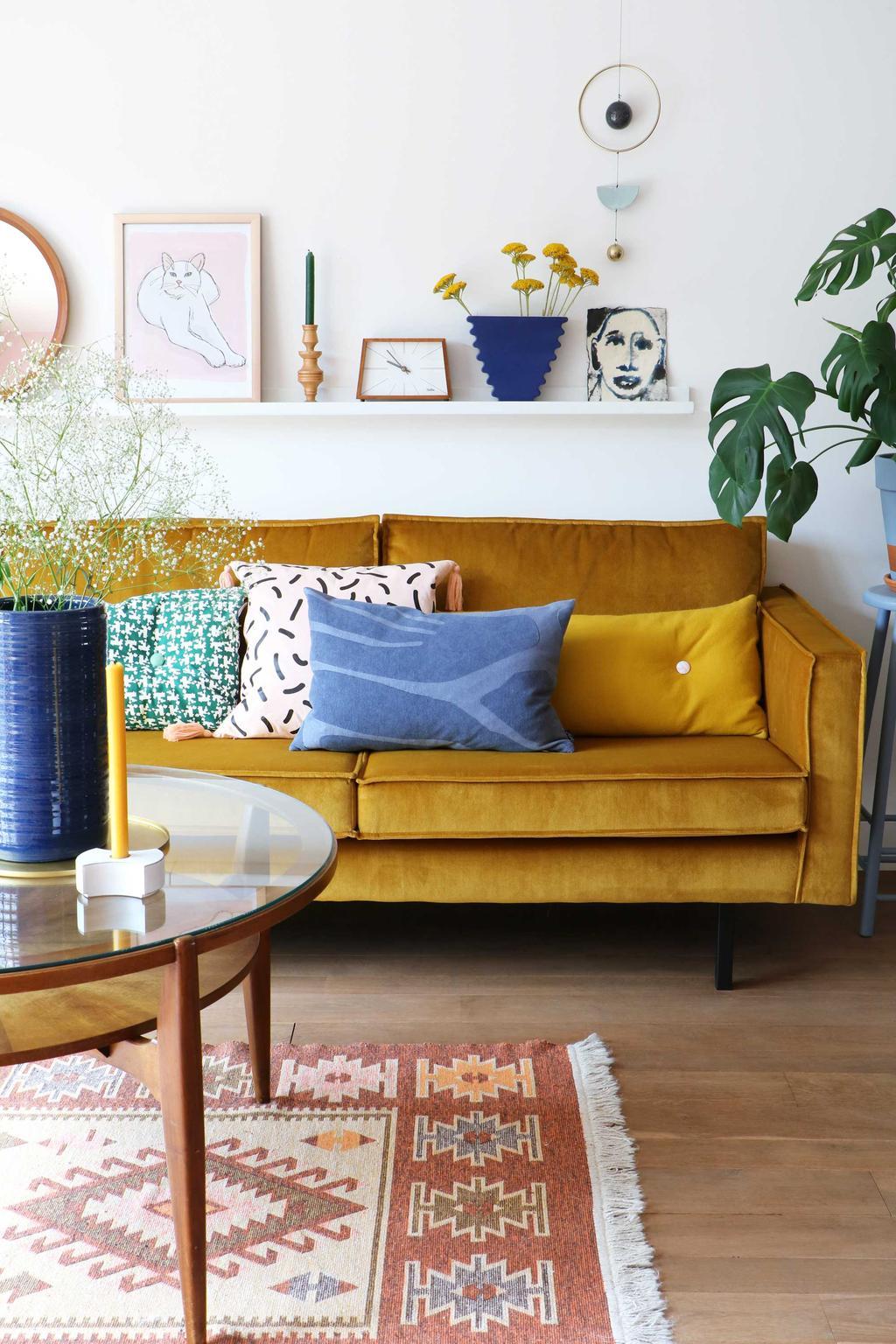 Woonkamer met oker gele bank en antiek tapijt