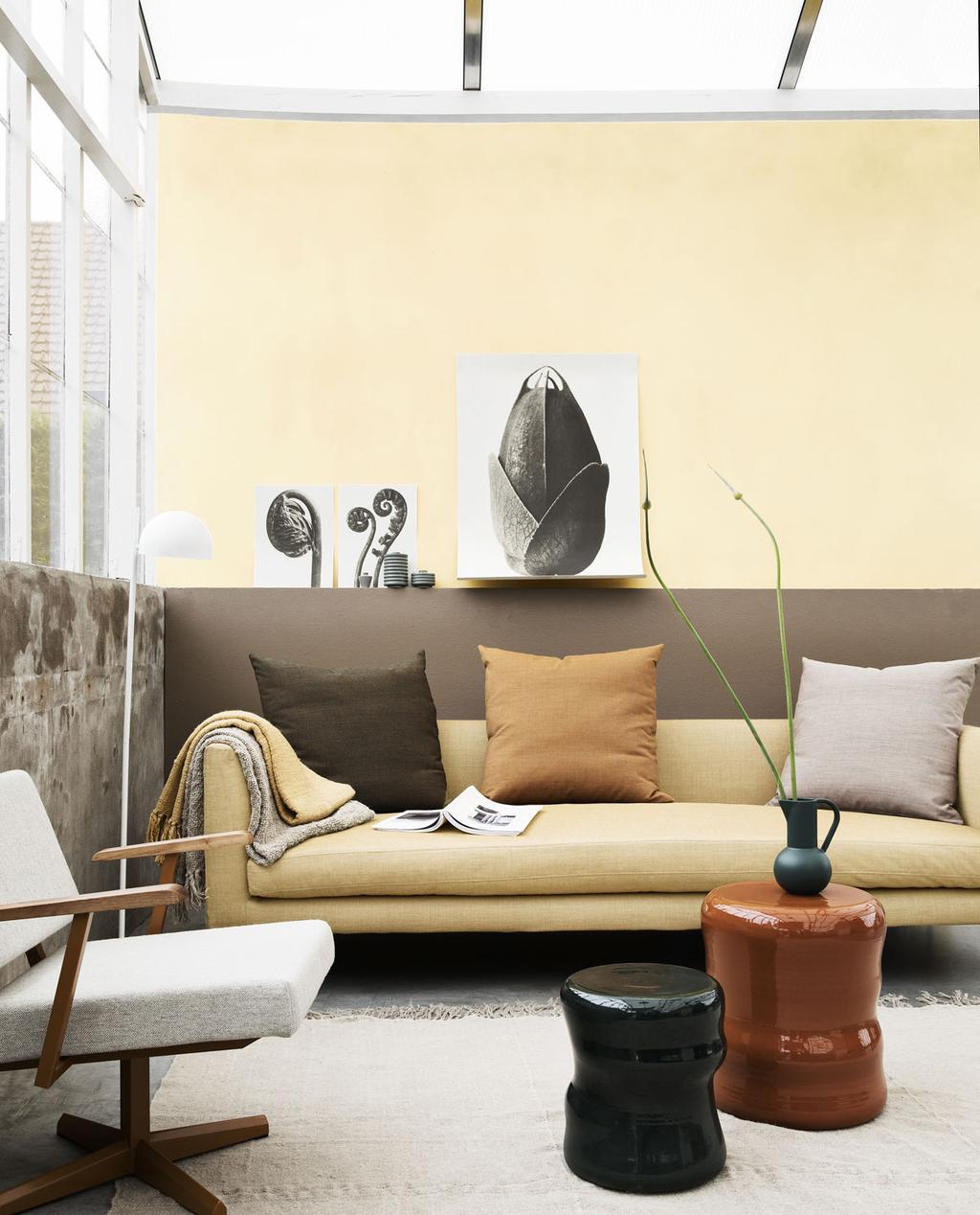 Woonkamer met pastelgele bank en muur als eyecatchers