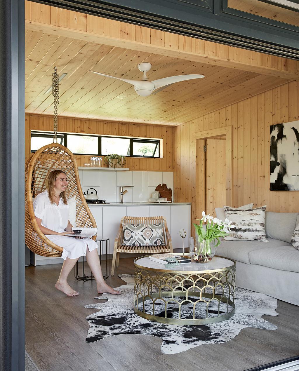 vtwonen special zomerhuizen 07-2021   hangstoel in de woonkamer met grijze bank