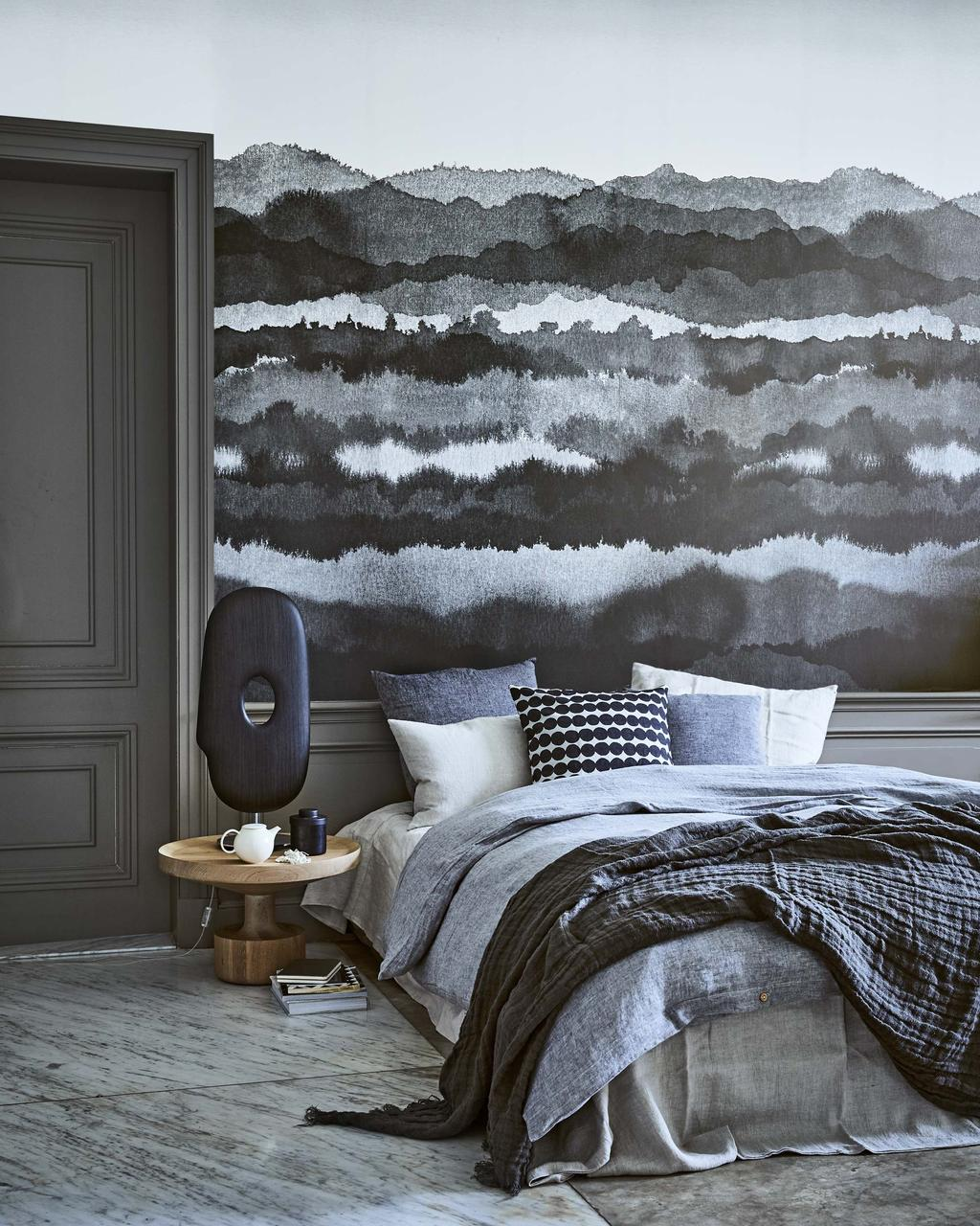 Donkere slaapkamer in de tinten grijs en zwart met kunst in huis