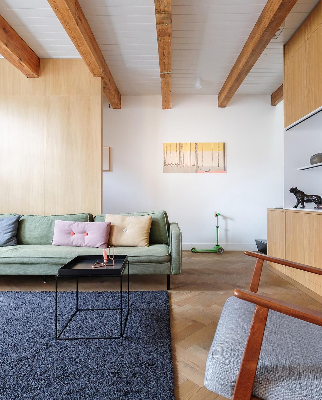 vtwonen 03-2021 | woonkamer met houten muren en groene bank, fauteuil en vloerkleed
