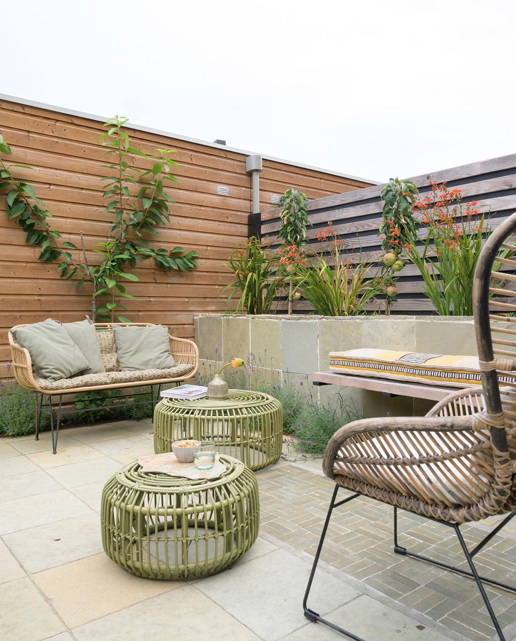 vtwonen 08-2021 | achtertuin stefanie en tommie met houten schutting en rotan tuinmeubilair