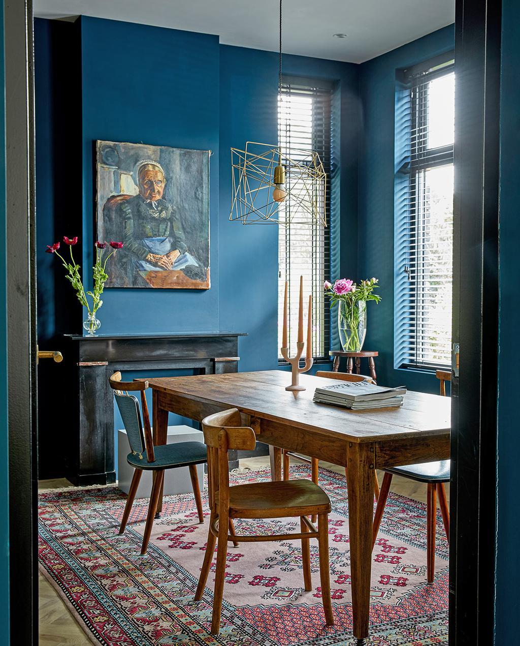 vtwonen 05-2021 | eettafel van hout met kunstwerk aan de blauwe muur