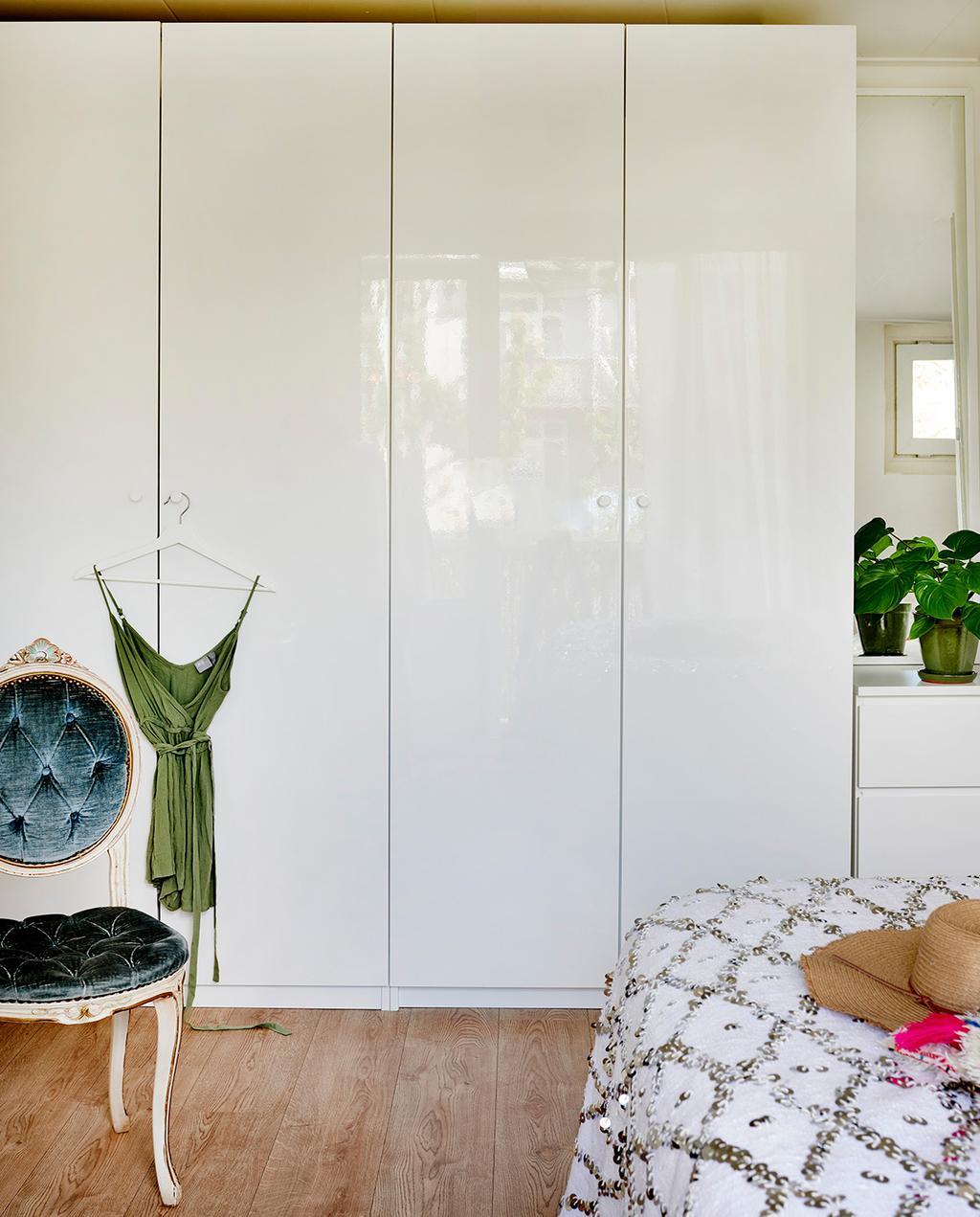 vtwonen special tiny houses | witte kast hoog met een groene jurk hangend aan de kast en een een velours stoel