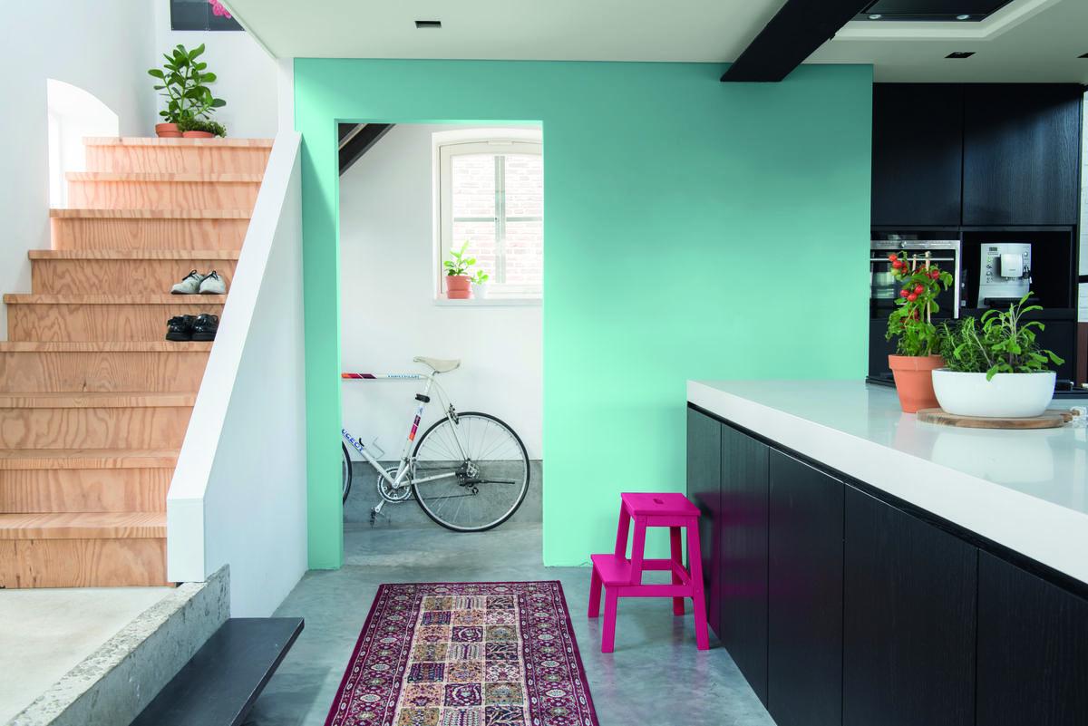 kleurentrends blauwe muur met doorkijk zwarte keuken grijze vloer tapijt houten trap