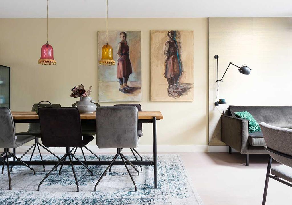 Eethoek met metallic behang, gekleurde hanglampen van glas en schilderijen