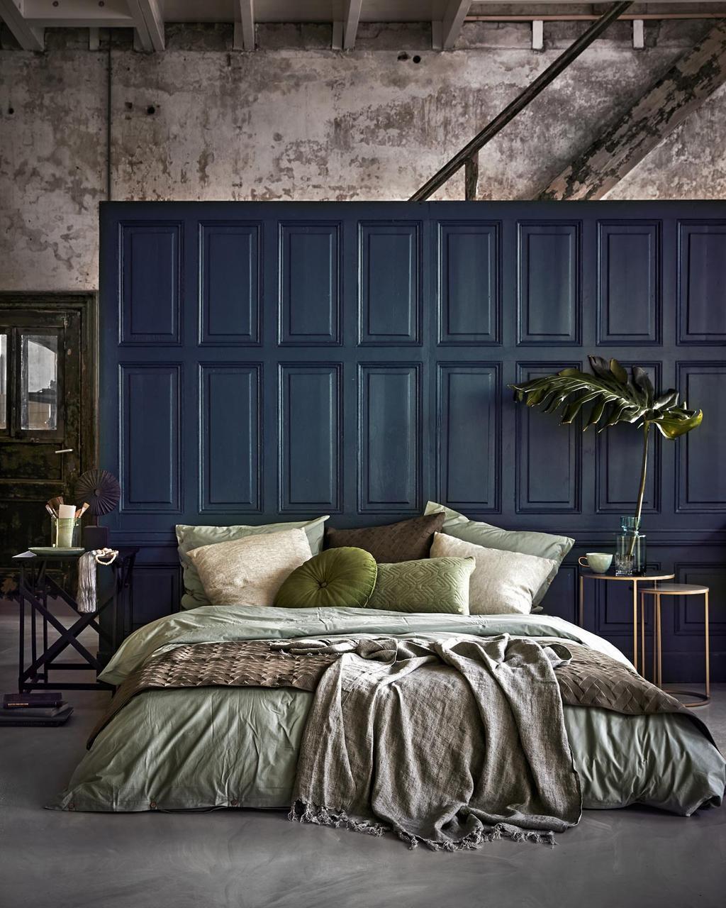 Een slaapkamer met donkere wand en linnen lakens
