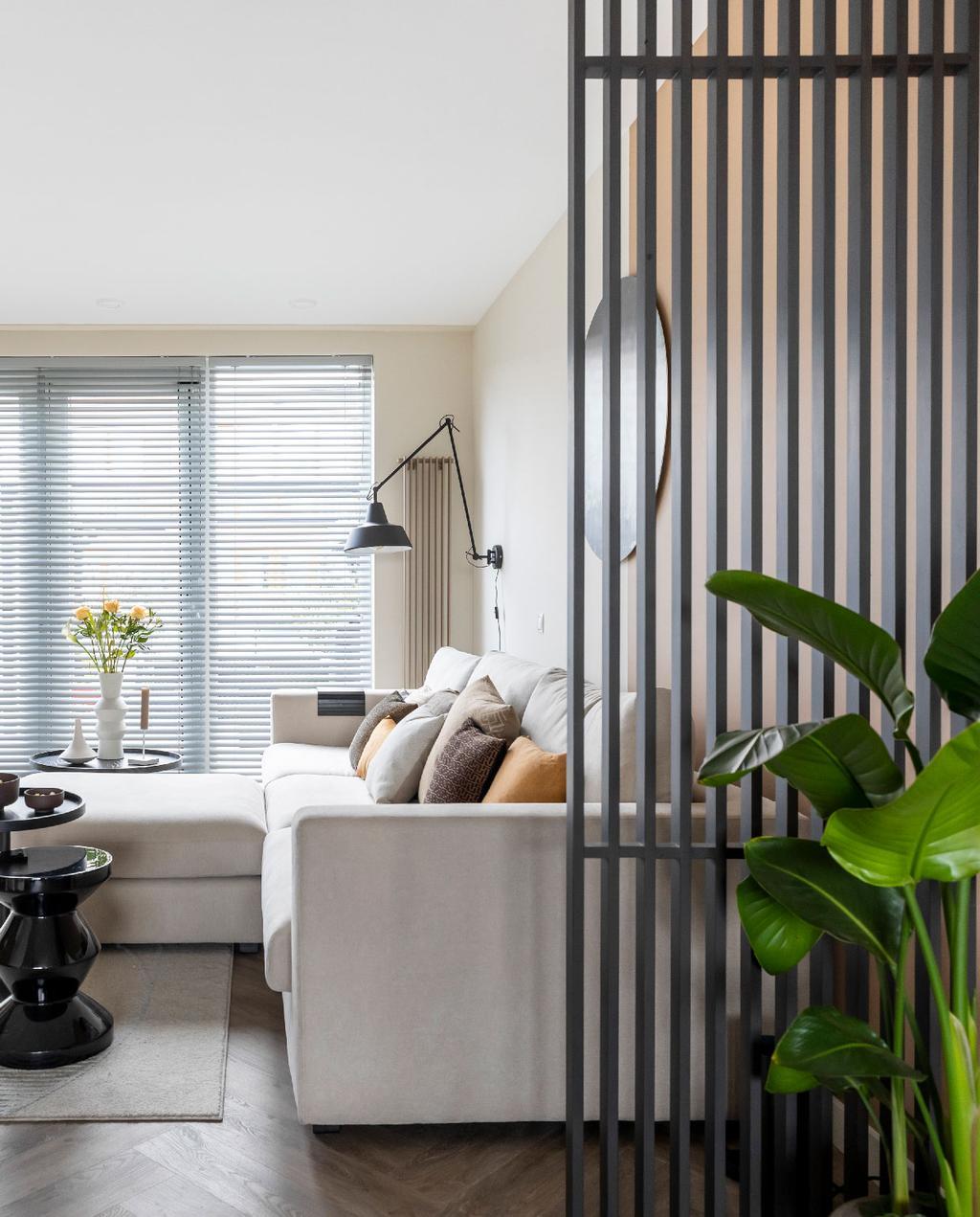 vtwonen weer verliefd op je huis uithoorn | neutrale woonkamer met witte bank, beige muur, grote kamerplant en houten latten als roomdivider