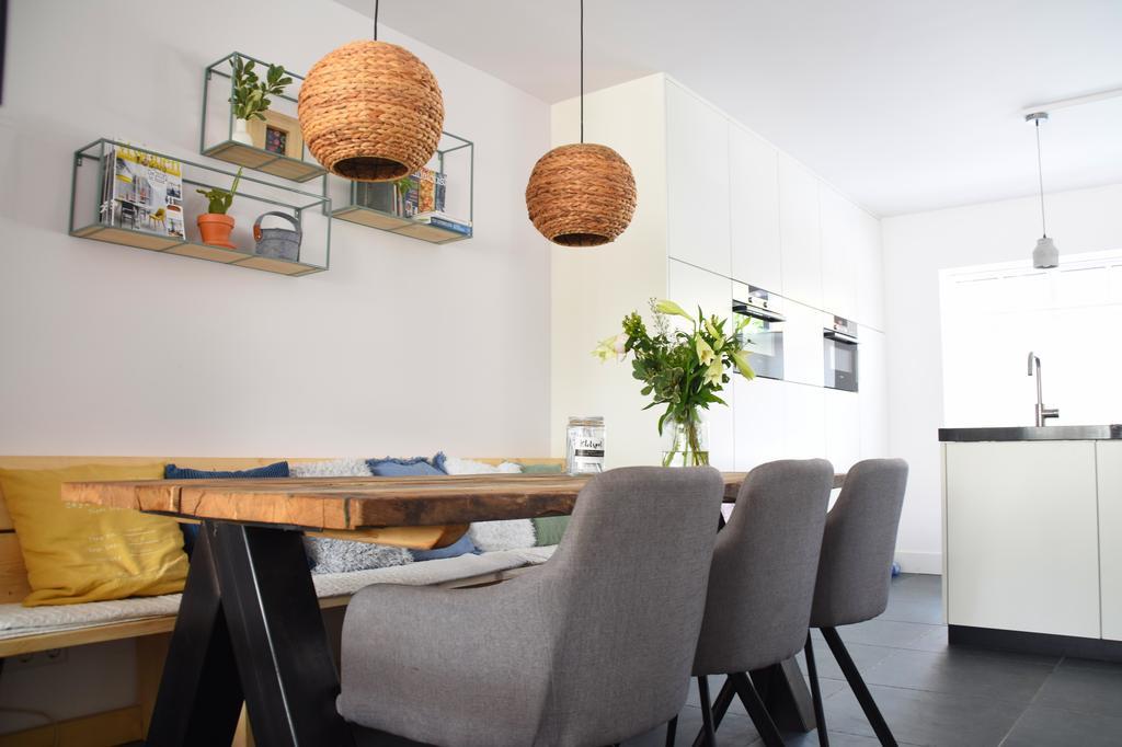 schappen-aan-de-muur-voor-quot-leesvoer-quot-en-ronde-lampen-van-zeegras-die-s-avonds-gezellig-op-de-tafel-schijnen