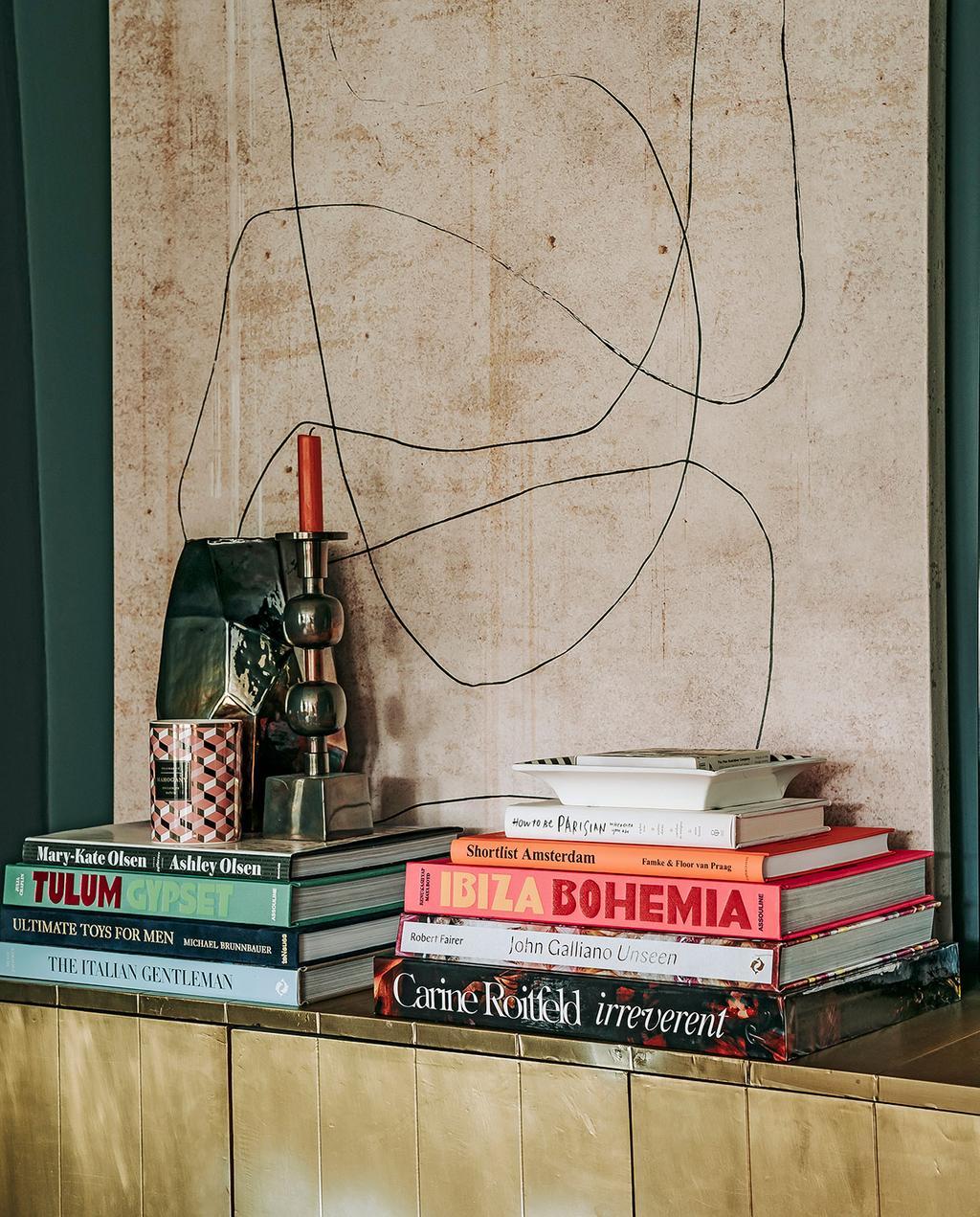 vtwonen 06-2021 | kunstwerk aan de wand met dressoir, kandelaar en boeken