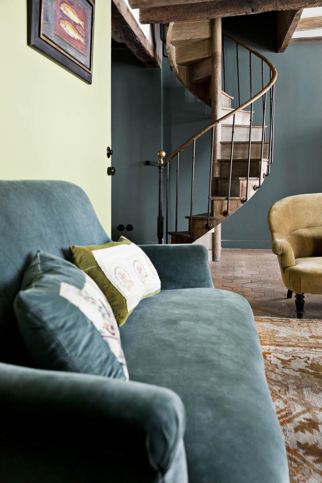 Houten ruimtebesparende trap in woonkamer met blauwe bank