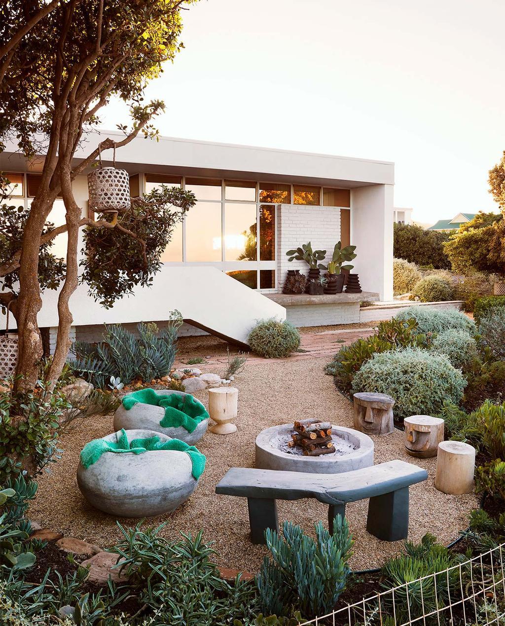 vtwonen special zomerhuizen 07-2021 | buitenkant van het huis met vuurkorf en zitplekken