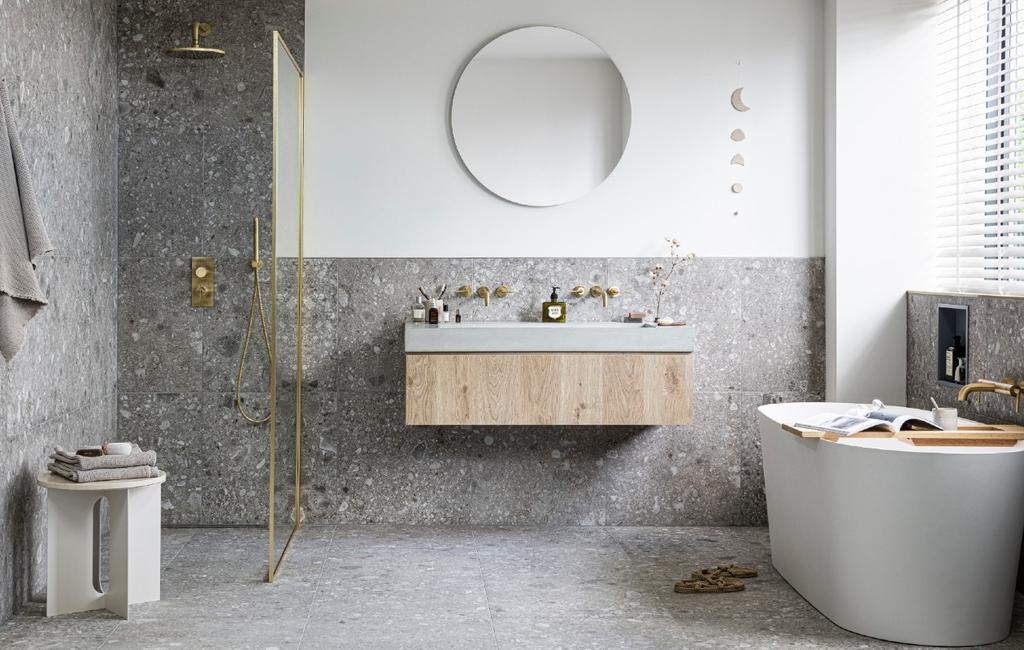 vtwonen collectie badkamer | grijze tegels, licht  houten wastafel en ronde spiegel
